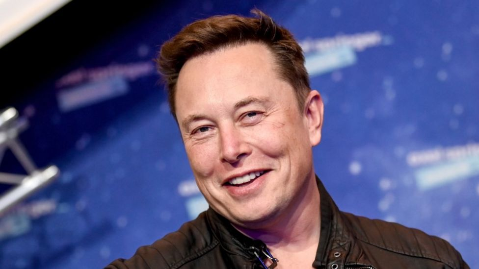Elon Musk Smiling against a blue background