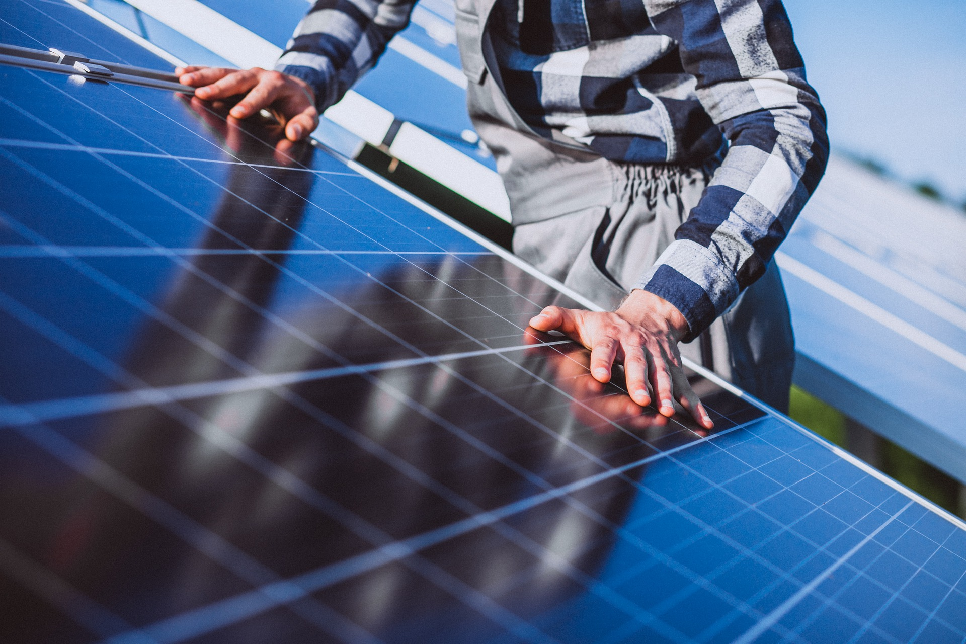 Man placing hands on solar panels on a rooftop